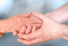 Mann hält Hände von eldery Frau Älteres Hilfs- und Unterstützungskonzept Lizenzfreie Stockfotografie