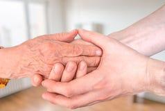 Mann hält Hände von eldery Frau Älteres Hilfs- und Unterstützungskonzept Lizenzfreies Stockfoto