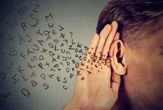 Mann hält Hand nahe Ohr hört sorgfältig die Alphabetbuchstaben, die herein fliegen stockfoto