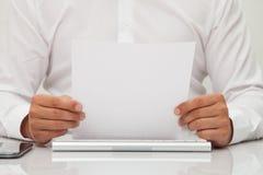 Mann hält leeres Blatt Papier in den Händen Stockbilder