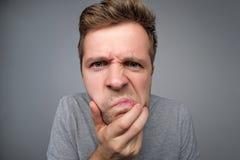 Mann hält Lippen gedrückt hat frustriert die Stirn gerunzeltes Gesicht lizenzfreie stockfotografie