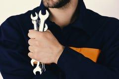 Mann hält Schlüsselwerkzeuge lokalisiert auf weißem Hintergrund Mechaniker oder Klempner mit metallischer Schlüsselausrüstung in  Stockbild