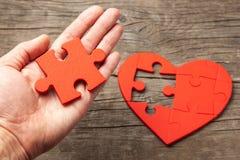 Mann hält in seinem Handteil des Puzzlespiels vom Herzen Wie man Ihren Seelenfreund oder Arbeit für die Seele findet lizenzfreie stockbilder