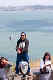 Mann hält Selfie-Stock, der Foto bei San Francisco Bay macht Lizenzfreie Stockfotos
