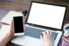 Mann hält Smartphone und schreibt auf Laptoptastatur Leere Bildschirme für das Montaging die Anwendungen lizenzfreies stockbild