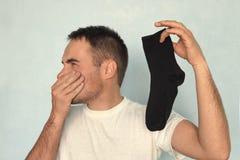 Mann hält Socken, schlechten Geruch von abgenutzten Socken Gestank, Gestank, Geruch, Gestank lizenzfreie stockfotos