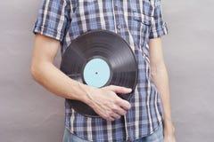 Mann hält Vinylaufzeichnung in seiner Hand Stockfotografie