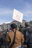 Mann hält Zeichen und umschlungenes Gewehr an. Stockbild