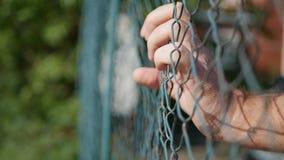 Mann-Hände, die in einem metallischen Zaun in einem Schutz-Bereich hängen lizenzfreie stockbilder