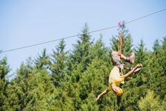 Mann-Hängen umgedreht auf Ziplinie Stockfoto