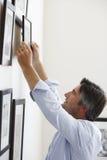 Mann-hängende Bilderrahmen auf Wand zu Hause Lizenzfreies Stockfoto