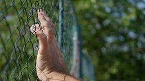 Mann-Handbild, das in einem metallischen Zaun hängt stockbilder