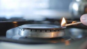 Mann-Handgebrauchs-Match für öffnendes Feuer auf einem Calor-Gas lizenzfreie stockfotos