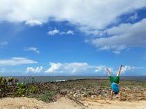 Mann Handstanding auf Strand als Wellenabbruch und Wolken im Himmel Lizenzfreies Stockbild