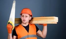 Mann, Heimwerker im Sturzhelm, Schutzhelm hält Handsaw, betrachtet scharfe Klinge, grauen Hintergrund Tischlerkonzept tischler Lizenzfreie Stockfotografie