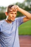 Mann in hellblauem T-Shirt Abwischen geschwitzt nachdem dem Laufen Stockbilder