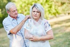 Mann hilft Frau mit dem gebrochenen Arm lizenzfreie stockfotografie