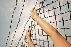 Mann hinter den Gefängnisstangen, die heraus erreichen Lizenzfreie Stockbilder