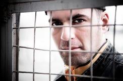 Mann hinter einem Eisen-Gitter Stockfotografie