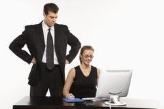 Mann hinter Frau am Computer Stockbild