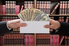 Mann-Hände, die Bestechungsgeld im Umschlag führen Lizenzfreie Stockfotografie