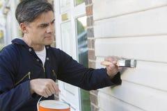 Mann-Holding-Bürste und Tin Painting Outside Of House Stockfotografie