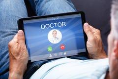 Mann-Holding-Digital-Tablet mit Call On Display Doktors stockfoto