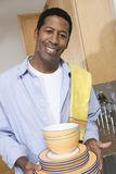 Mann-Holding-Stapel gewaschene Platten Stockbilder