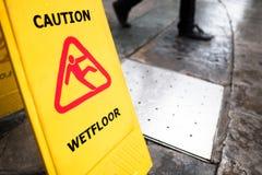 ` Mann-Ikonenbeleg auf nassem Boden `, gelber Plastikstand Signage Stockfotos
