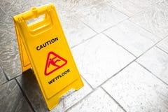 ` Mann-Ikonenbeleg auf nassem Boden `, gelber Plastikstand Signage Stockbilder