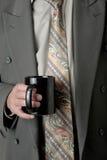 Mann im Anzug, der einen Tasse Kaffee anhält Stockbild