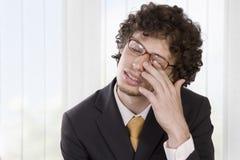 Mann im Anzug sein Auge massierend, um zu entlasten Stockbilder