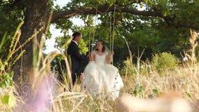 Mann im Anzug und Frau im weißen Heiratskleid sind glückliches Fahren auf Schwingen Braut und Bräutigam in der Liebe stehen herei stock footage