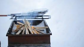 Mann im aufpassenden Feuer des Winters, das im Grill ausgebrochen wird und setzt ihn in das Anzünden ein stock footage