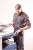 Mann im Büro, das Kopien unter Verwendung des Fotokopierers erstellt Stockbild