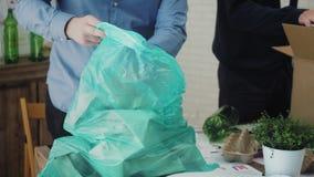 Mann im Büro, das Papierabfall in die Wiederverwertung der Tasche einsetzt stock video