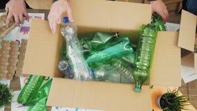 Mann im Büro, das Plastikabfall in Wiederverwertungsbehälter einsetzt stock video