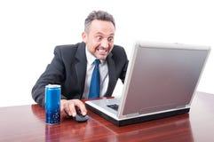 Mann im Büro mit dem psychotischen Blick, der Energiegetränk hat Stockfotografie