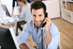 Mann im Büro sprechend am Telefon stockbild