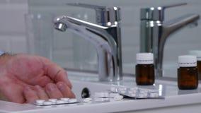 Mann im Badezimmer ausgewählt und einige Pillen für eine medizinische Heilung nehmen stock footage