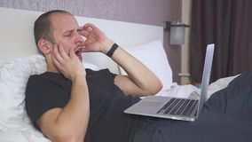Mann im Bett, das an Laptop und möchten arbeitet wirklich, schlafen, reibt seine Augen stock video footage