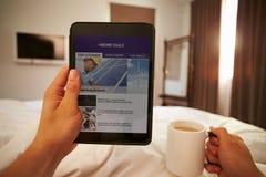 Mann im Bett, das Nachrichten-Website auf Digital-Tablet betrachtet stockfotografie