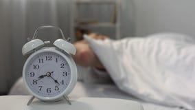 Mann im Bett, das zu Klingelnwecker, gesunder Lebensstil, Disziplin aufwacht stock video