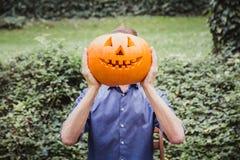 Mann im blauen Hemd, das großen Kürbis vor seinem Gesicht hält Glückliches Halloween lizenzfreie stockbilder