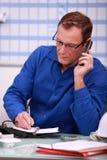 Mann im blauen Overallsprechen Lizenzfreies Stockfoto