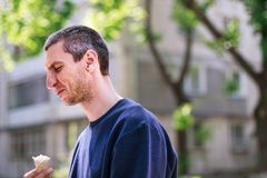 Mann im blauen pulover Eiscreme im Park essend stockfotos