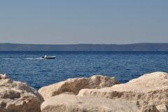 Mann im Boot auf dem Meer Lizenzfreie Stockfotos