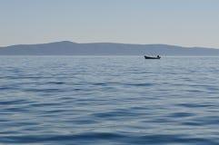 Mann im Boot auf dem Meer Stockbild