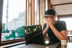 Mann im Café sitzt bei Tisch mit Computer nahe Fenster und verstecktem Gesicht durch Hände lizenzfreies stockbild