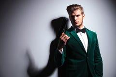 Mann im eleganten grünen Samtanzug, der ein großes Gewehr hält Lizenzfreie Stockfotografie